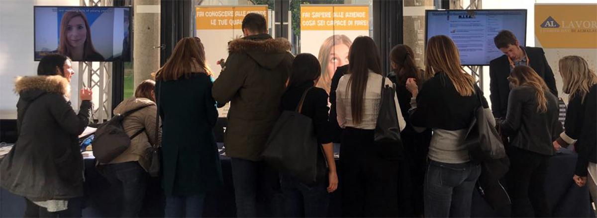 Giovani al banco accoglienza di un career day di AlmaLaurea